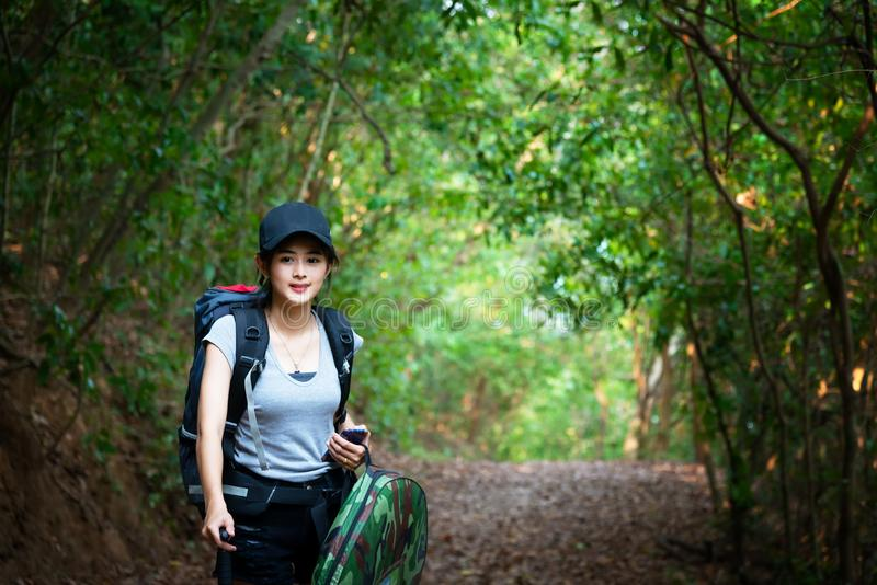 Hiker young women walking in national park outdoors with backpack. Woman tourist going camping in forest. royalty free stock photography