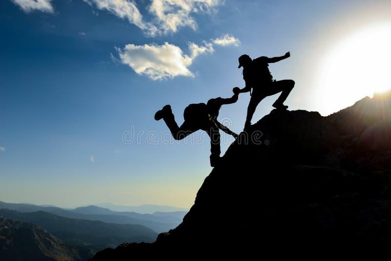 Hikers взбираясь на горе Помощь, риск, поддержка, помощь стоковая фотография