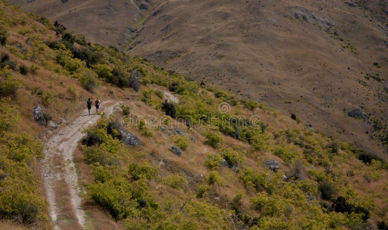 2 hikers в расстоянии на пути к Mt Пизе около Cromwell в Новой Зеландии стоковая фотография rf