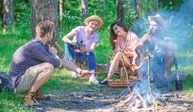 Hikers деля впечатление прогулки и еды Поход выходных Пикник с друзьями в лесе около костра Компания имея стоковые изображения rf