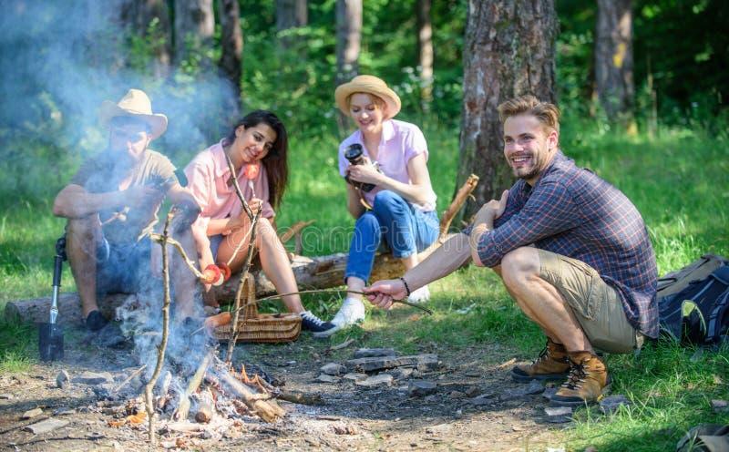 Hikers деля впечатление прогулки и еды Поход лета Пикник с друзьями в лесе около костра Компания имея стоковая фотография