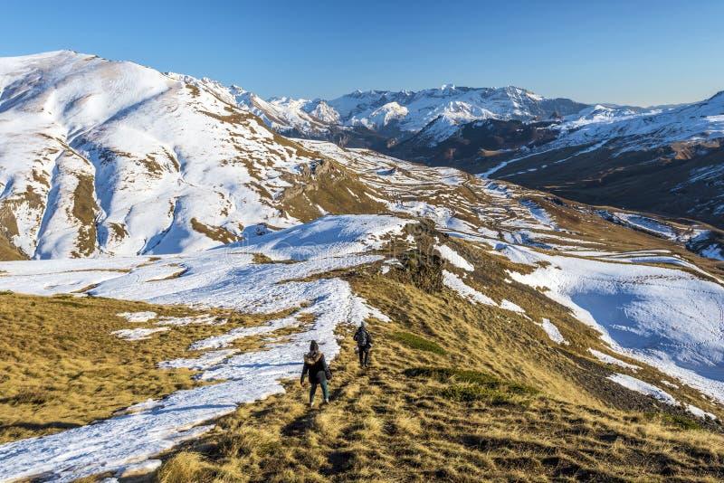 Hikers людей двигая вниз от наклона горы в испанский Арагон Пиренеи Предыдущий ландшафт зимы долины Tena на стоковая фотография