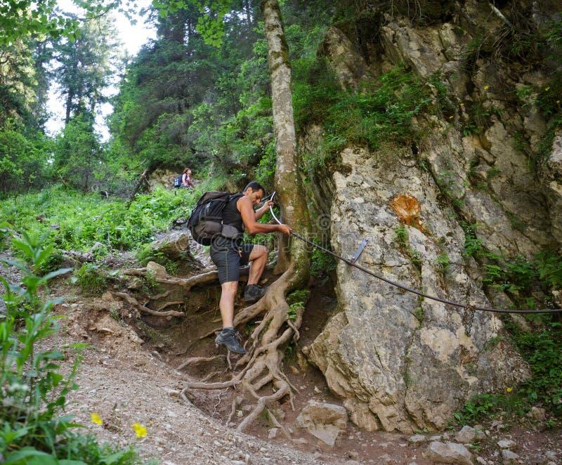 Hikers на опасном следе, держа линию безопасности стоковое фото rf
