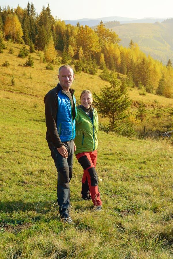 Hikers отдыхают в горах осени Счастливые пары стоковое фото rf