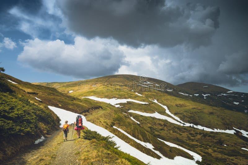 Hikers семьи идя дорогой в горах весны стоковое изображение