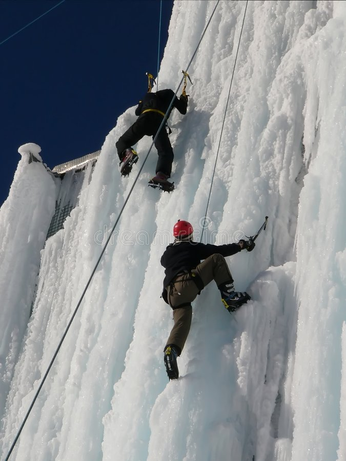 Hikers. Photo of two hikers climbing the ice wall royalty free stock photos