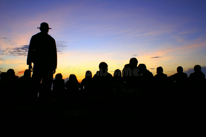 Hikers admiring sunrise. Group of hikers on mountain top at dawn admiring sunrise, people in silhouette royalty free stock photography