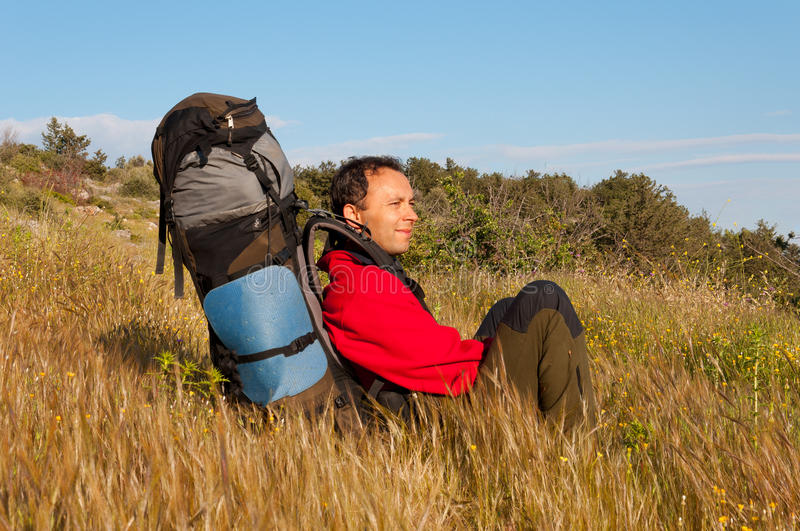 Hikers with backpack sitting on grass in mountain and looking into the distance royalty free stock photo