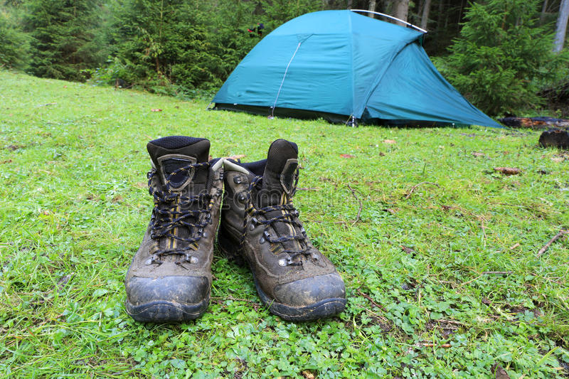 Hikers boots on green meadow stock images