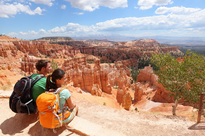 Hikers in Bryce Canyon resting enjoying view. Hiking couple in beautiful nature landscape with hoodoos, pinnacles and spires rock formations. Bryce Canyon stock photo