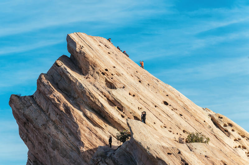 Hikers climbing on rock formations at Vasquez Rocks Natural Area Park. Visitors clamber on a giant rock shark fin-like formation at the popular park near Santa royalty free stock photo