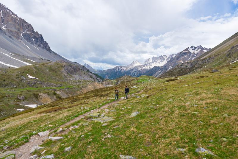 Hikers climbing uphill on steep rocky mountain trail. Summer adventures and exploration on the Alps. Dramatic sky with storm cloud royalty free stock image