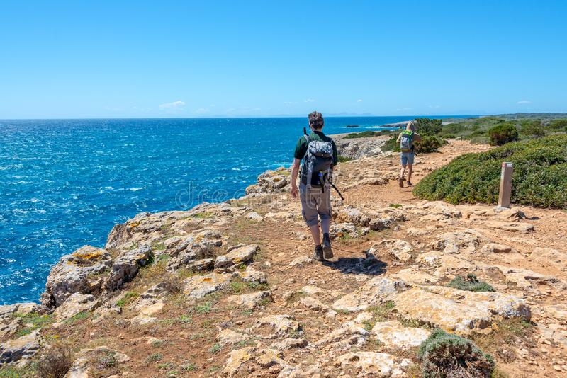 Hikers on a coastal path by the sea in Menorca, Balearic islands Spain. Hikers on a coastal path by the sea in Menorca, Balearic islands, Spain stock image
