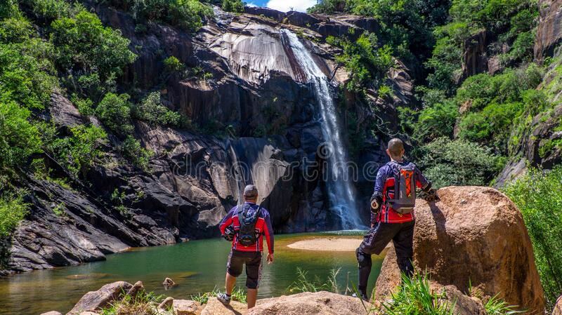 Hikers by countryside waterfall royalty free stock photos