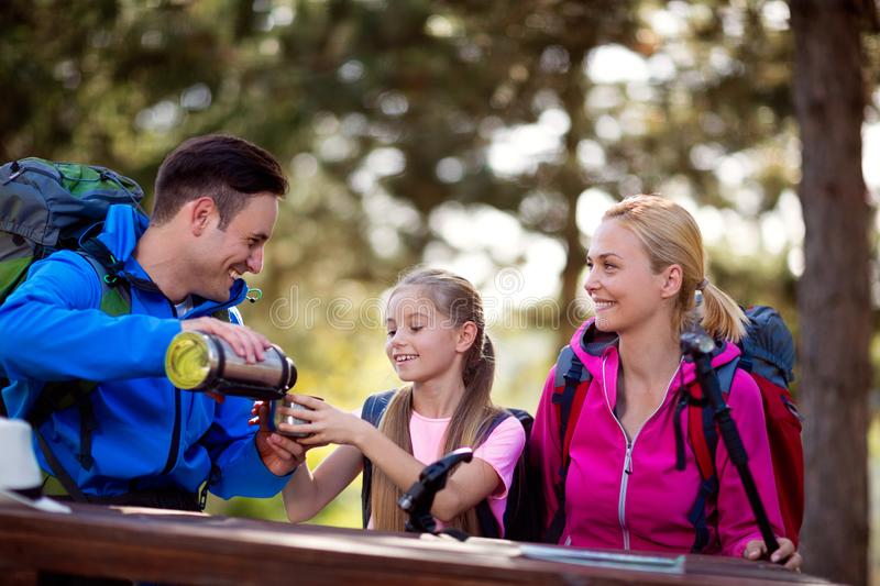Hikers father gives drink to her child royalty free stock image