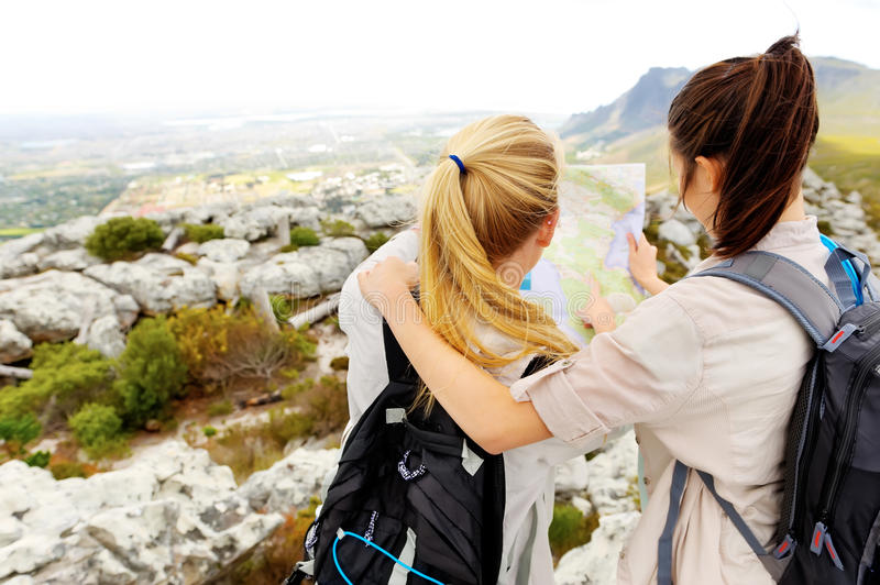 Hikers getting lost. Friends try to find their bearings on a map while hiking outdoors. leading a healthy lifestyle royalty free stock photos