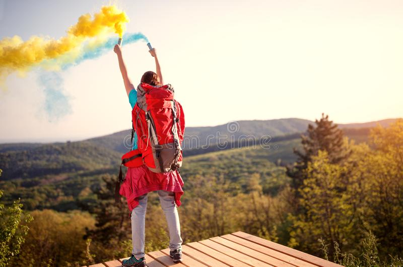 Hikers girl with hands up holding torch with yellow and blue smoke stock photo