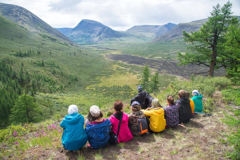 Hikers have a rest on a hillside with beautiful view to the mountains, people relax on summer activity. royalty free stock photo