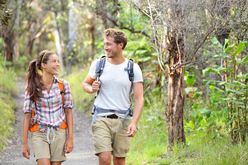 Hikers - hiking people walking happy in forest royalty free stock photography