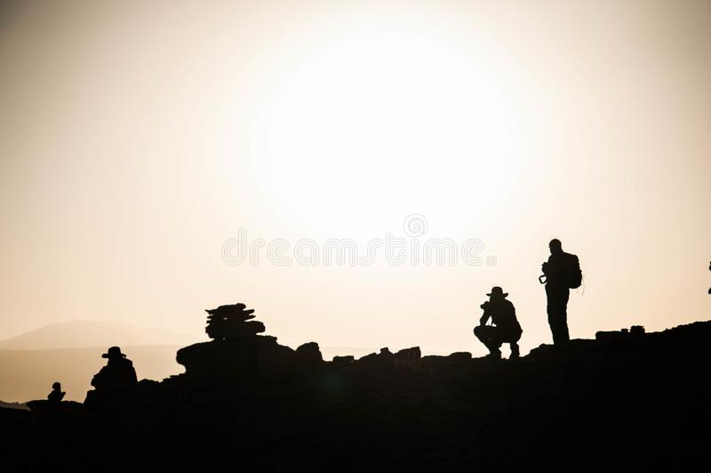 Hikers on hilltop in Atacama Desert. Silhouettes of hikers on a rocky hilltop in the Atacama Desert, Chile stock photos