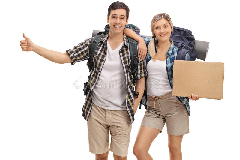 Hikers hitchhiking and holding a blank cardboard sign. Cheerful hikers hitchhiking and holding a blank cardboard sign isolated on white background stock image