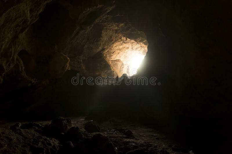 Hikers in a huge cave. Hikers at the entrance of huge cave, backlighted, near Hpan, Myanmar royalty free stock photos