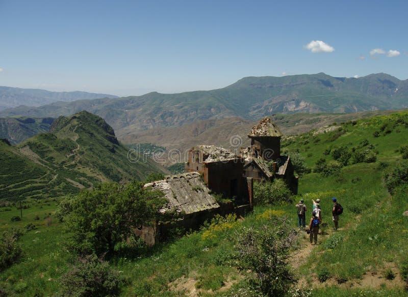 Hikers at Medieval Church Ruins. Hikers arrive at the ruins of the medieval Tsakhats Kar monastery near Artabuynk, Armenia royalty free stock photos