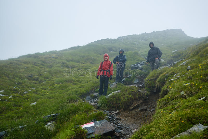 Hikers in raincoats on mountain stock image