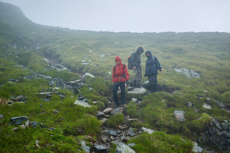 Hikers in raincoats on mountain royalty free stock photography