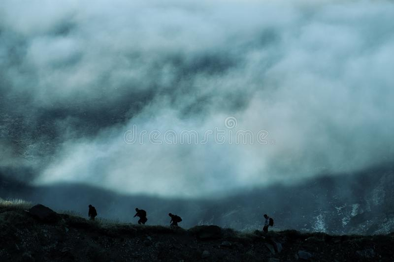 Hikers In Raw Climbing High Altitude Trial Above Low Clouds. Silhouette hikers in a raw climbing high altitude trial above low clouds in Etna Park, Sicily royalty free stock photos
