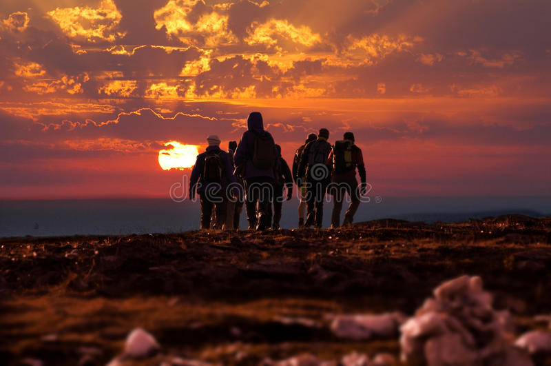 Hikers reach mountain top at sunset. Group of hikers walking at sunset stock photography