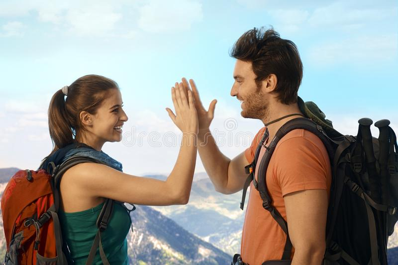 Hikers reached the destination in mountains. Young hikers celebrating reach of destination in mountains royalty free stock images