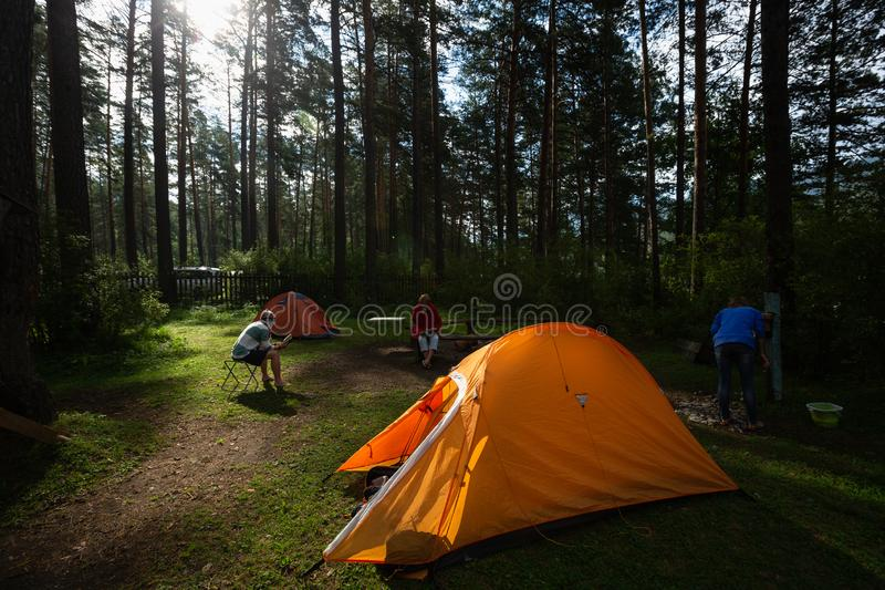 Hikers relax in a camp. Set on the meadow in a forest stock photos
