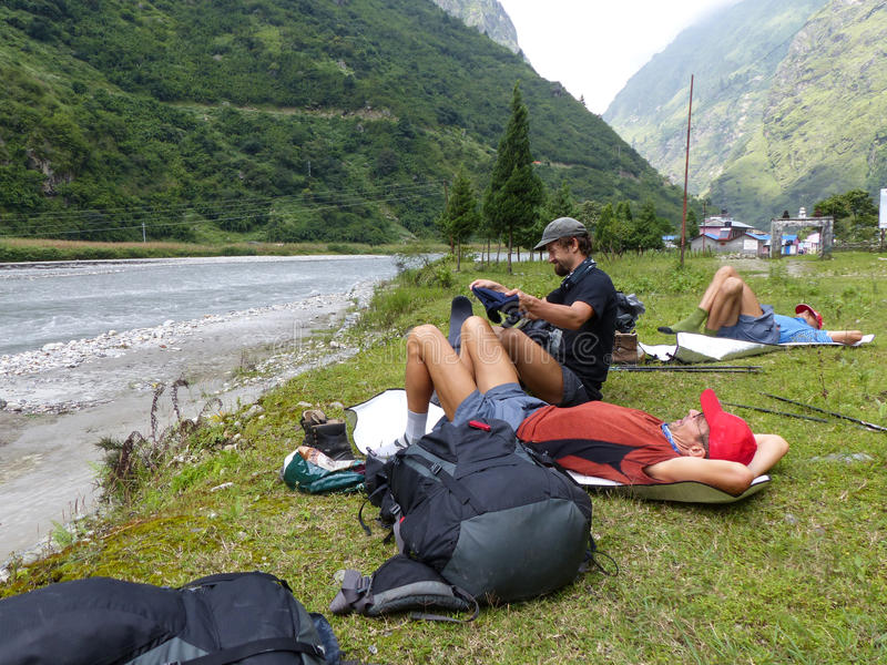 Hikers relaxing near river in Tal village in Nepal. Little village in Nepal - Marsyangdi river valley - Annapurna Circuit trek in Nepal stock images
