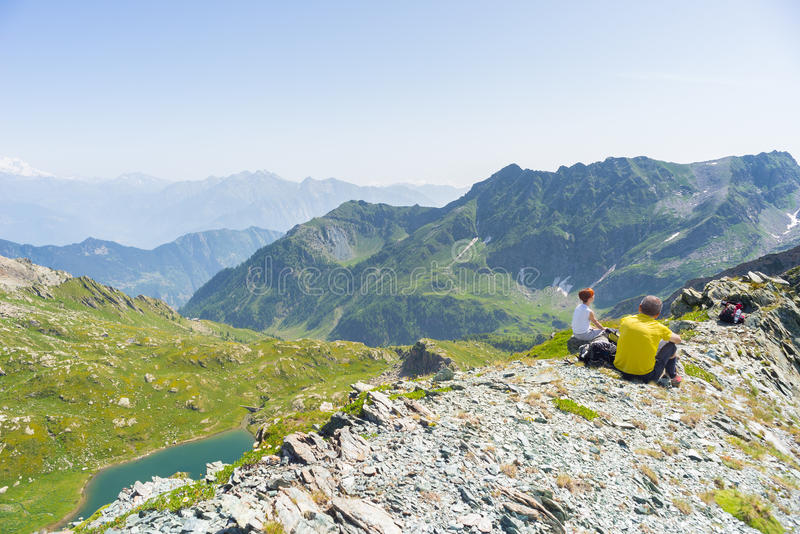 Hikers resting on the mountain summit, expansive panorama royalty free stock photos