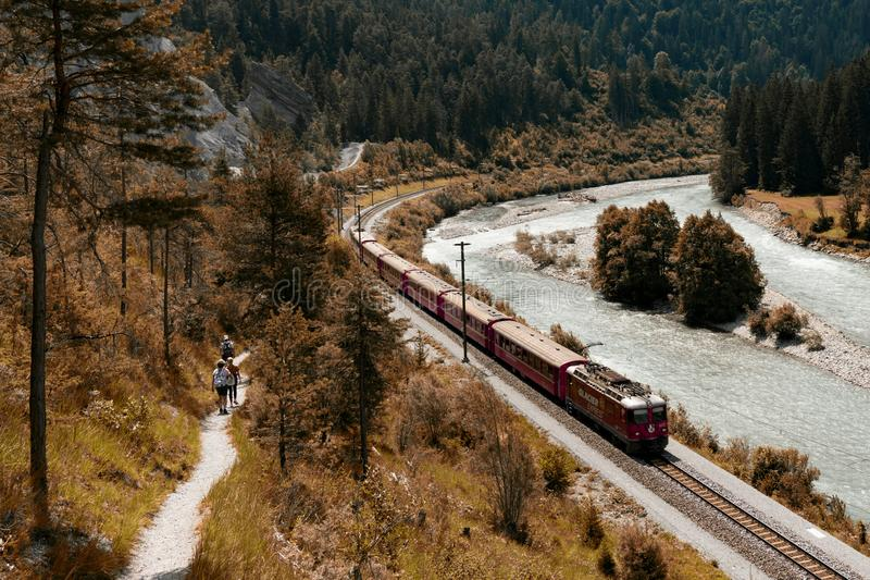 Hikers and the Rhaetian railway on the banks of the Rhine River in the Ruinaulta Gorge stock photo