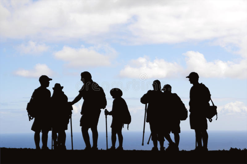 Hikers Silhouette. A grouping of hikers on a mountain ridge are silhouetted against the ocean and blue skyline. Ample space is provided for headlines or text royalty free stock photography