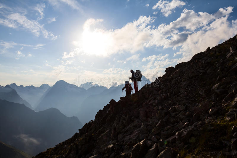 Hikers silhouette on a mountain slope. In a mist royalty free stock image