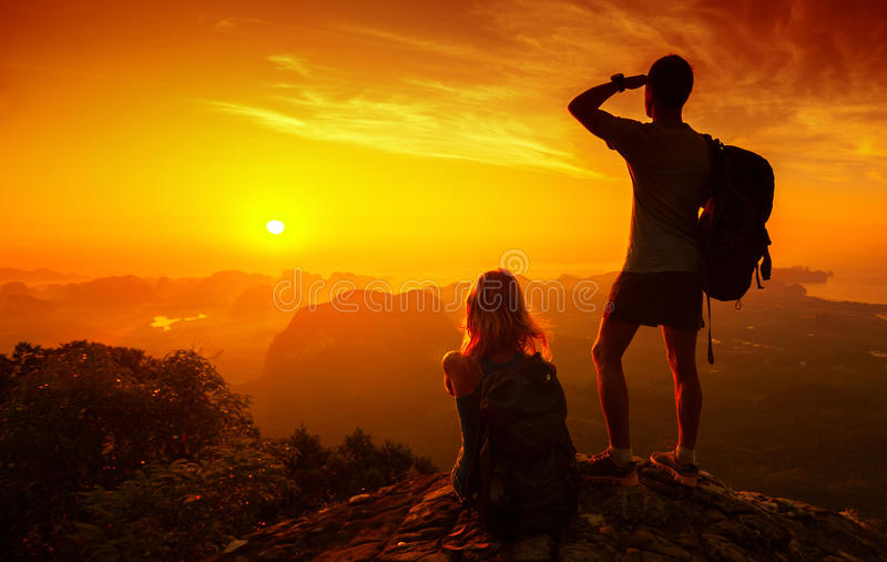 Hikers. Silhouette of hikers standing on top of hill and enjoying sunrise over the valley royalty free stock images
