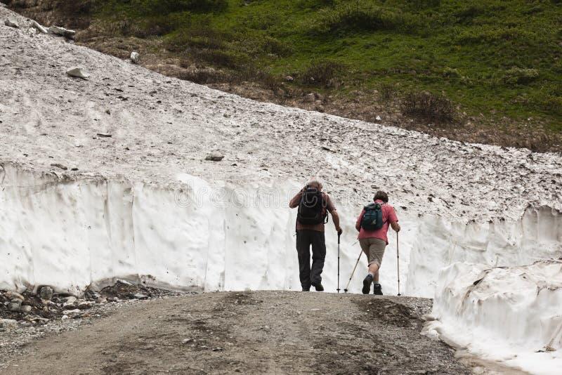 Hikers between snow in Koednitz Valley, Austria royalty free stock images
