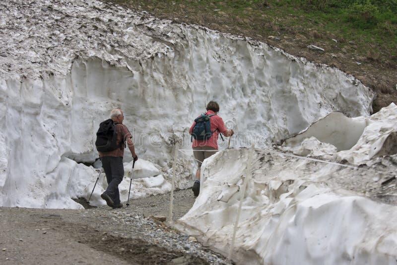 Hikers between snow, Koednitz Valley, Austria stock image