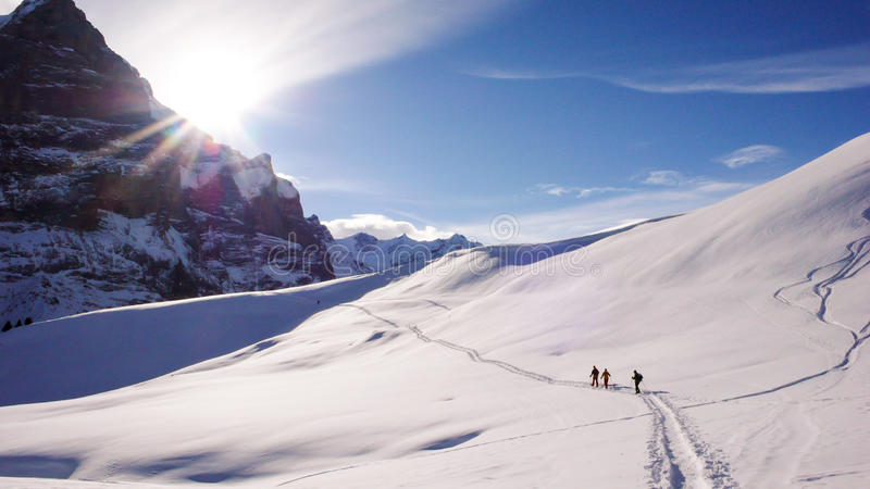 Hikers snowshoeing at the foot of the Eiger north face in the Swiss Alps near Grindelwald stock photos