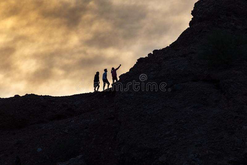 Hikers take a selfie. Against a dramatic sunset background at Papago Park in Phoenix, Arizona stock images