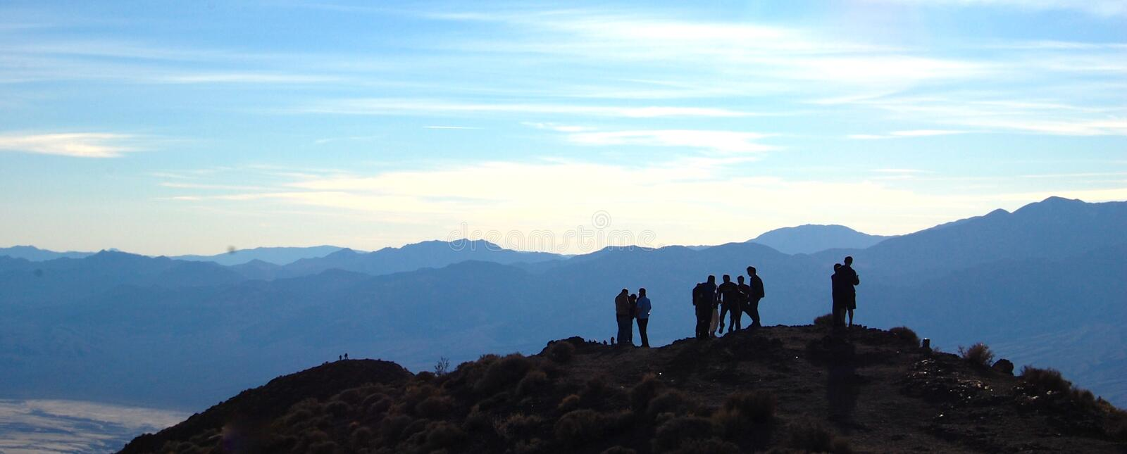 Hikers Taking Pleasure in Their View from the Top. Captivating landscape with hikers in the front creating a silhouette stock image