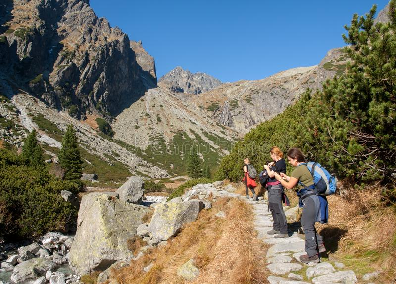 Hikers on trail at Valley of Five Spis Lakes. High Tatra Mountains, Slovakia. Vysoke Tatry, Slovakia - October 10, 2018: Hikers on trail at Valley of Five Spis stock photography