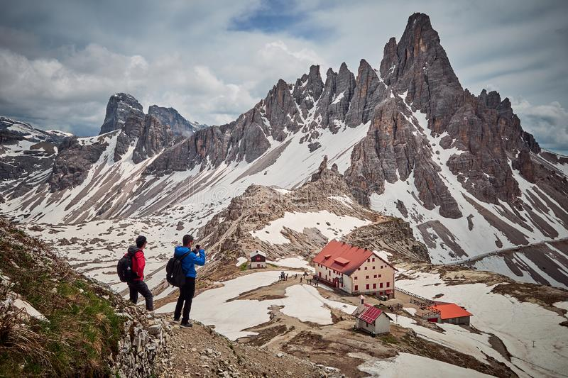 Hikers with Tre Cime di Lavaredo in the background, Dolomites, Italy stock photo