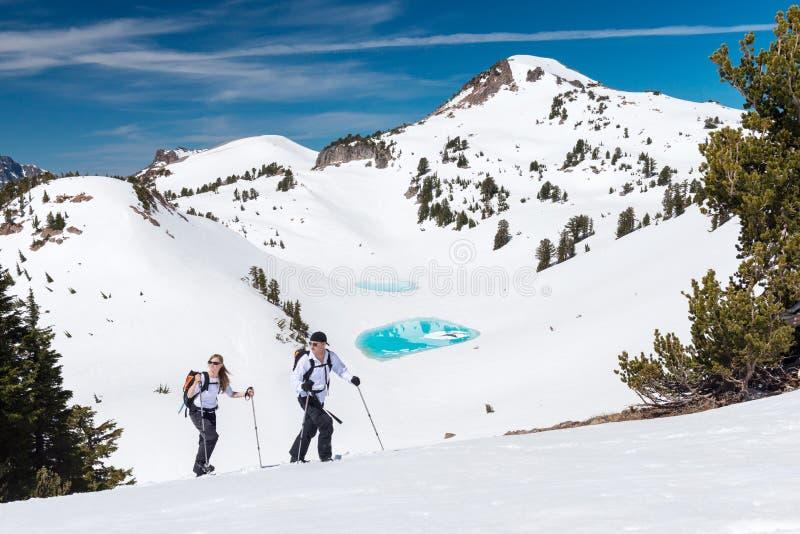 Hikers Trek Through a Winter Mountain Landscape. A pair of hikers trek across a snowy mountain landscape stock photo