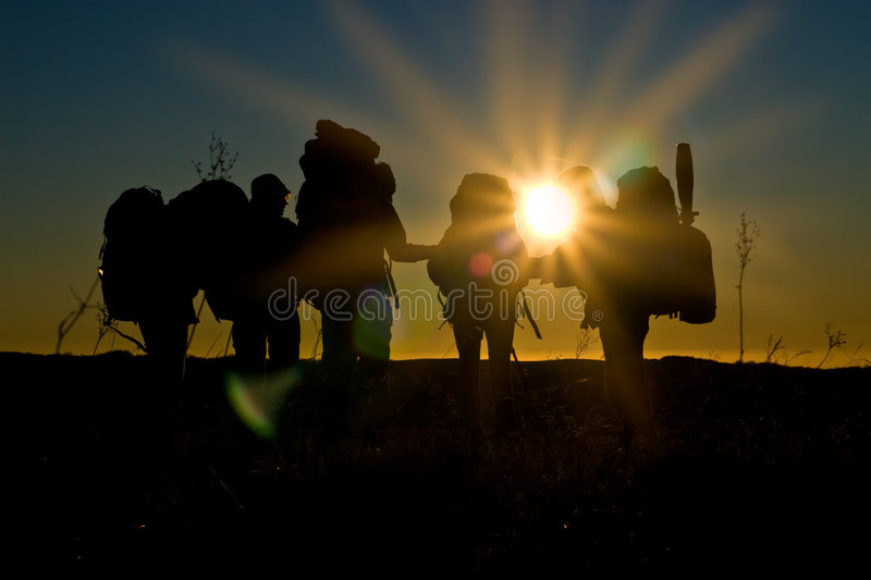 Hikers walk in sunset with sunbeams royalty free stock image