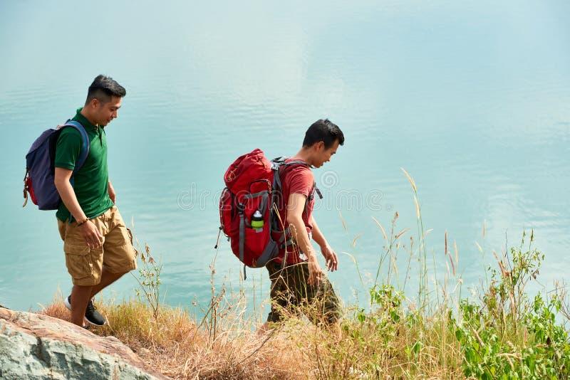 Hikers walking along lake stock images