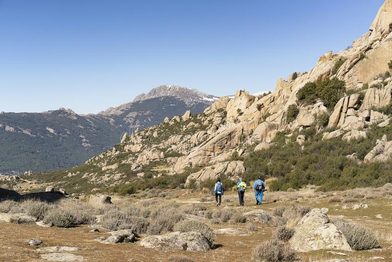 Hikers walking in a path in La Pedriza, National Park of mountain range of Guadarrama in Manzanares El Real, Madrid, Spain stock images